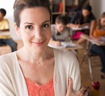 Photo of a teacher smiling in front of class